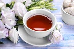 与一杯茶和甜点的白花南北美洲香草在蓝色木背景 免版税库存图片