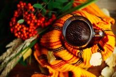 与一杯茶的秋天背景与黄色叶子的和温暖在老委员会的被编织的围巾与拷贝的窗口背景的 库存照片