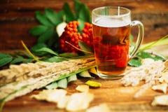 与一杯茶的秋天背景与黄色叶子的和温暖在老委员会的被编织的围巾与拷贝的窗口背景的 免版税库存照片