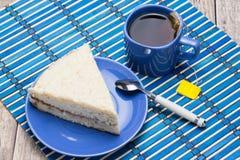 与一杯茶的鲜美饼在一张桌上的以黑暗 库存照片