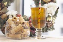 与一杯茶,碗曲奇饼和花圈的一个明亮的早晨 免版税库存照片