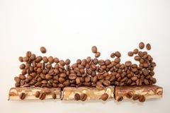 与一枚坚果的甜糖果在白色的咖啡粒 库存照片
