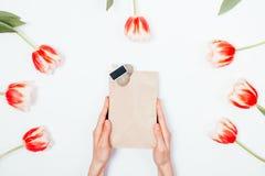 与一枚徽章的礼物纸袋在女性手上 免版税图库摄影