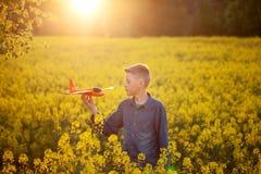 与一架玩具飞机的儿童游戏在旅途日落和梦想在夏日 免版税库存照片