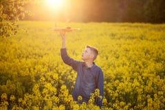与一架玩具飞机的儿童游戏在旅途日落和梦想在夏日 图库摄影