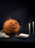 与一根抽烟的香烟的万圣夜南瓜在他的嘴 恶习 免版税库存照片