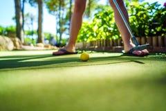 与一根棒的微型高尔夫球黄色球在日落 库存图片