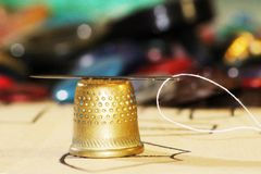 与一根穿线的针的老黄铜顶针 免版税库存图片
