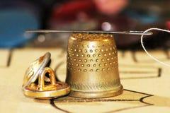 与一根穿线的针的老黄铜顶针 免版税库存照片