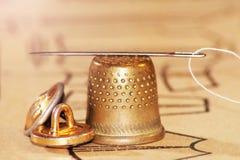 与一根穿线的针的老黄铜顶针 库存照片