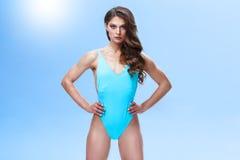 与一根运动的身体和长的头发的女性健身模型在一个轻的演播室摆在 照片在五颜六色被做和 免版税库存照片