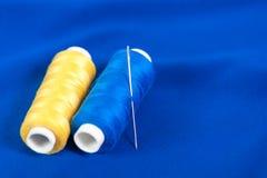 与一根针的黄色和蓝色螺纹在纺织品 免版税库存图片