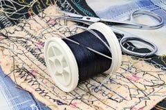 与一根针的黑螺纹在塑料短管轴和剪刀在裁缝的工作表上 免版税库存照片