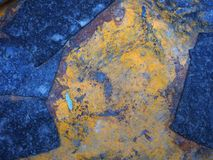 与一棵树的一片小叶子的抽象明亮的黄色和蓝色金属背景在中部 老被绘的金属背景,表面 免版税库存图片