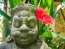 与一棵红色木槿的监护人雕象,泰国 免版税图库摄影