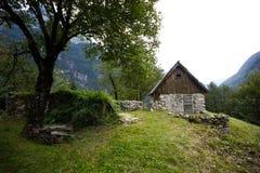 与一棵老树的老山小屋在中间遥远的山谷的前面,阿尔卑斯,斯洛文尼亚 免版税库存照片