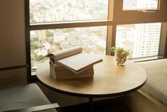与一棵被打开的书和植物的木桌窗口的 库存图片