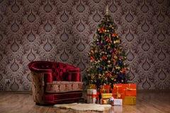 与一棵装饰的圣诞树、礼物和扶手椅子的黑暗的圣诞节场面 免版税库存图片