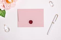 与一次长方形轻碰的桃红色信封,大模型 给封印、笔、花和婚礼装饰打蜡 免版税库存照片