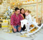 与一点女儿的年轻家庭在家一起获得乐趣在圣诞树附近 免版税库存图片
