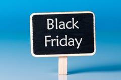 与一点木标记的黑星期五购物销售概念 销售标记关闭在蓝色背景 背景看板卡问候页购物模板时间普遍性万维网 天与 库存照片