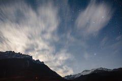 与一点雪的山在上面和移动的云彩在与星的蓝色颜色夜在Lachung的冬天在北部锡金 免版税图库摄影