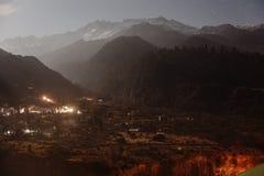 与一点雪的山在与下面被点燃的村庄的上面在Lachung的冬天夜在北部锡金,印度 免版税库存照片