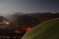 与一点雪的山在与下面被点燃的村庄的上面在Lachung的冬天夜在北部锡金,印度 免版税图库摄影