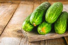 与一片叶子的新鲜的黄瓜在一张老木桌上 免版税库存照片