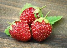 与一片叶子的草莓在木桌上 免版税库存图片