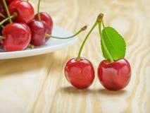 与一片绿色叶子的两棵成熟红色樱桃在一块白色板材旁边用樱桃填装了 背景轻的木头 免版税库存图片