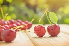 与一片绿色叶子的两棵成熟红色樱桃 驱散在桌堆樱桃 在背景中,鲜绿色的叶子 免版税库存图片