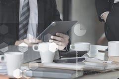 与一种数字式片剂的手指触摸屏的商人在桌上的办公室与文件图表数据 免版税图库摄影