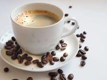 与一粒白色杯子和棕色豆的咖啡在茶碟 免版税库存照片