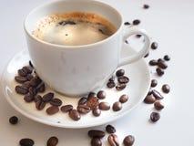 与一粒白色杯子和棕色豆的咖啡在茶碟 免版税库存图片