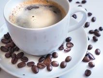 与一粒白色杯子和棕色豆的咖啡在茶碟 图库摄影