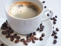 与一粒白色杯子和棕色豆的咖啡在茶碟 库存图片