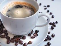 与一粒白色杯子和棕色豆的咖啡在茶碟 库存照片