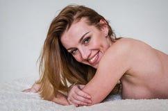 与一美好的微笑和长的头发性感说谎的年轻美好的性感的女孩模型在与赤裸乳房的床上 免版税库存图片