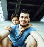 与一起使用小逗人喜爱的儿子的年轻俏丽的人模型,锂 免版税库存图片