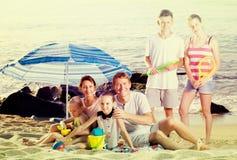 与一起孩子的活跃家庭在海滩开会 免版税库存照片