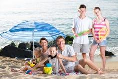 与一起孩子的活跃家庭在海滩开会 库存图片