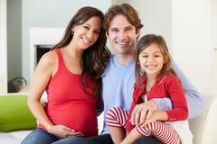 与一起放松在沙发的怀孕的母亲的家庭 免版税库存照片