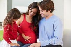与一起放松在沙发的怀孕的母亲的家庭 库存图片