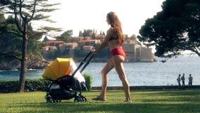 与一辆婴儿推车的年轻女人佩带的游泳衣旅行沿海边在度假 股票视频