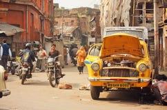 与一辆汽车的事故在有多灰尘的城市的步行者和骑自行车的人的一条拥挤的街上 库存图片