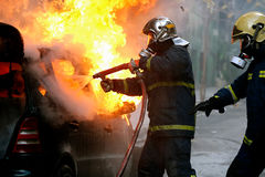 与一辆火焰状汽车战斗的消防员在爆炸以后 库存照片