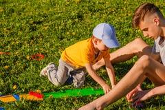 与一辆玩具汽车的两兄弟戏剧在绿草草坪 免版税库存图片