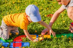 与一辆玩具汽车的两兄弟戏剧在绿草草坪 免版税图库摄影
