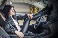 与一辆白色汽车的美好的性感的女性模型在停车场 库存图片